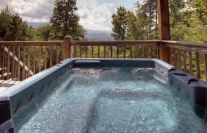A hot tub on the deck of a Pigeon Forge cabin with mountain views.