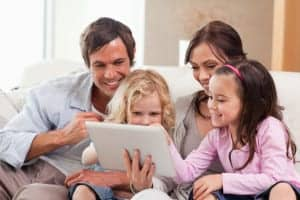 Family using a tablet together on the couch.
